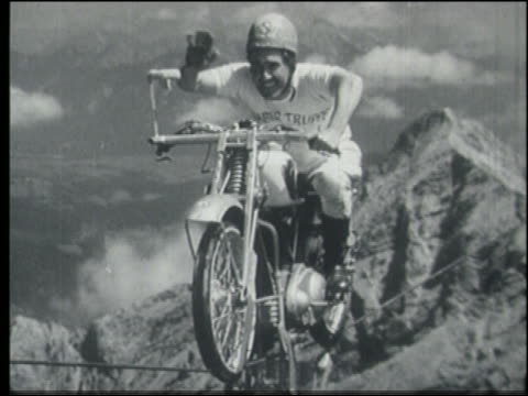 b/w man on motorcycle on tightrope over alps waving to camera - stunt person stock videos & royalty-free footage