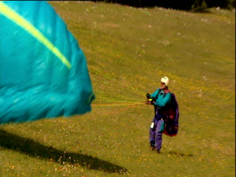 man on mountainside sets up parachute zoom out to man turning and running to take off parascending into valley below - österreichische kultur stock-videos und b-roll-filmmaterial
