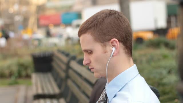 vídeos y material grabado en eventos de stock de man on park bench listening to music - enfoque en primer plano