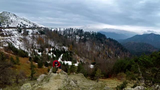 Man On Peak Of Mountain - Searching Backpack - 4K Resolution
