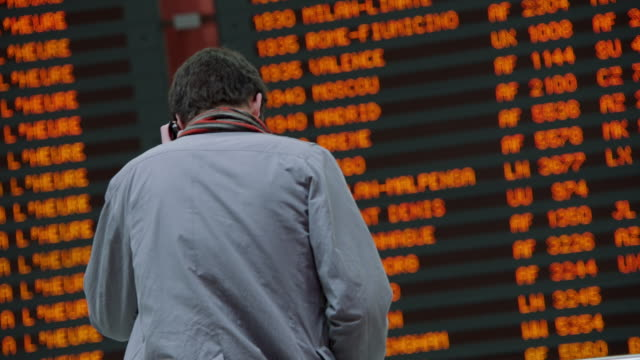 MS R/F Man on phone in front of departure board