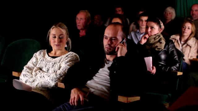 Mann auf Handy inCinema/Kino, beobachten film