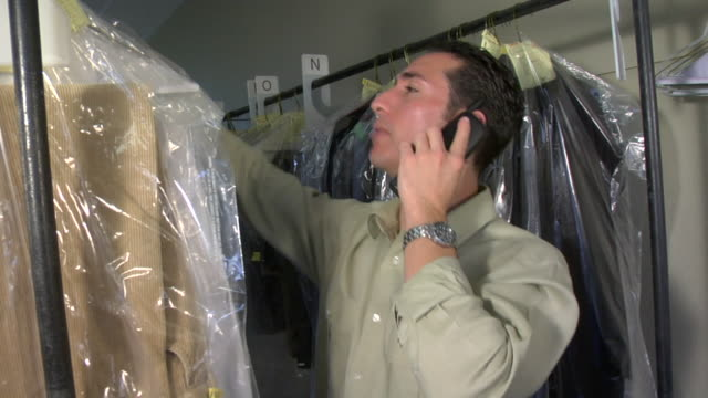stockvideo's en b-roll-footage met cu, man on phone working at dry cleaners, santa fe, new mexico, usa - draadloze telefoon