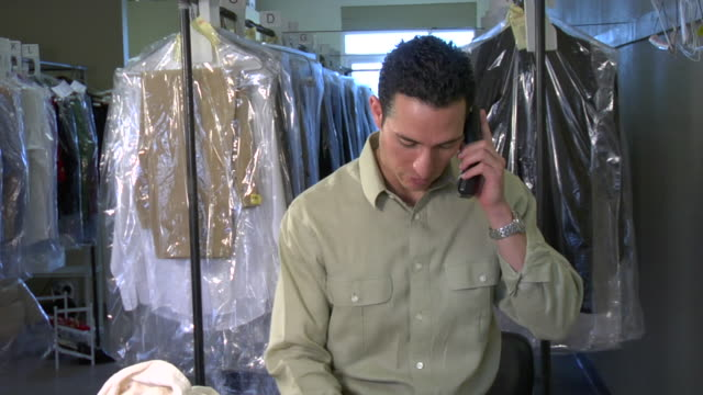 ZI, CU, Man on phone working at dry cleaners, Santa Fe, New Mexico, USA