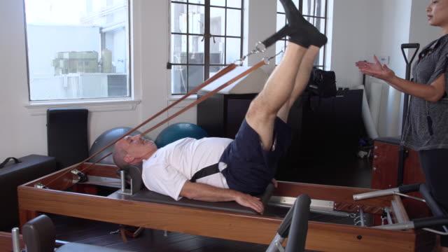 "vidéos et rushes de ""ms man on pilates reformer doing leg exercising with female instructor / beverly hills, california, united states"" - instructeur"