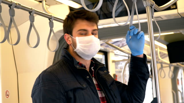 man on public transportation vehicle with face mask and protective glove. - mode of transport stock videos & royalty-free footage