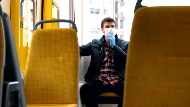 man on public transportation vehicle with face mask and protective glove. - train vehicle stock videos & royalty-free footage