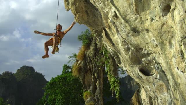 vídeos de stock e filmes b-roll de ws man on rock face being lowered down by rope / krabi, thailand - braço humano