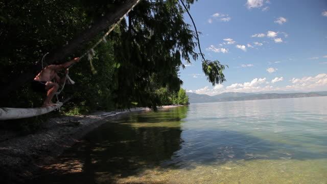 WS TS Man on rope swinging into lake / Idaho, United States