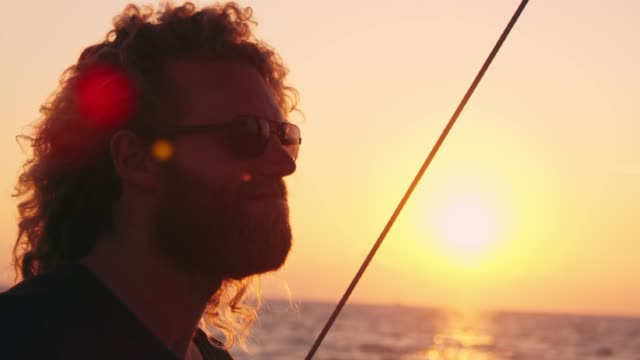 4k man on sailboat on sunny, tranquil sunset ocean, slow motion - yachting stock videos & royalty-free footage