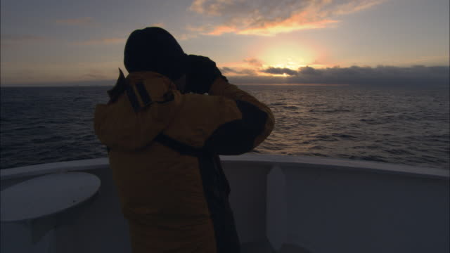 CU, Man on ship at sunset, looking through binoculars, rear view, Antarctica