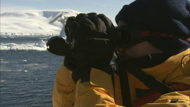 cu, man on ship looking through binoculars, antarctica - antarctica research stock videos & royalty-free footage