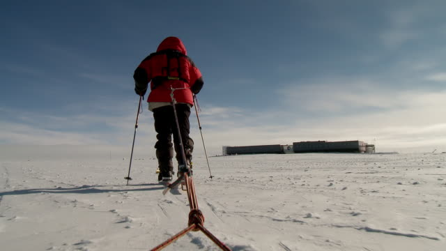 ms la pov of man on skis pulling pack sleds across south pole ice with us south pole base in distance / south pole, antarctica - south pole stock videos & royalty-free footage