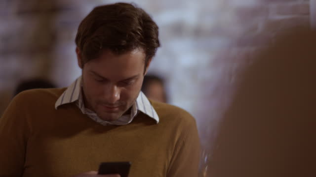 Man on smartphone ignores friends at restaurant table
