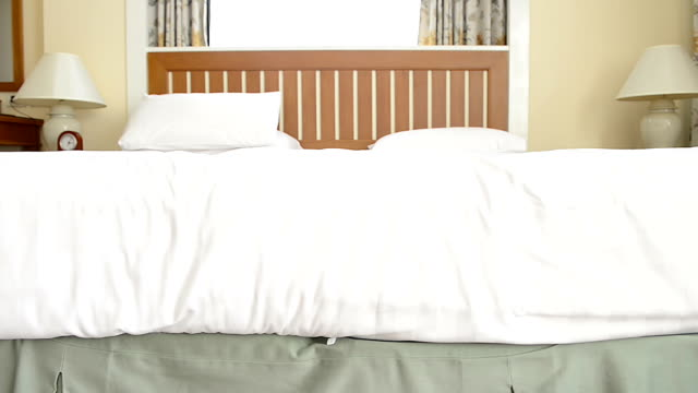 Man on smoothing a fresh white bedding