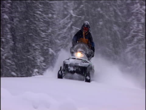 Man on snowmobile going though heavy snow in mountain area