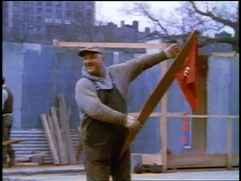 "1957 man on street holding ""con edison"" flag waving + smiling on nyc street - 1957 video stock e b–roll"