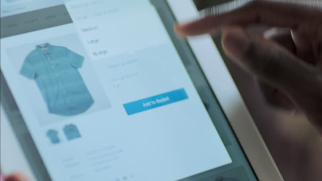 vídeos de stock e filmes b-roll de man on tablet adds shirt to basket in online store - e commerce