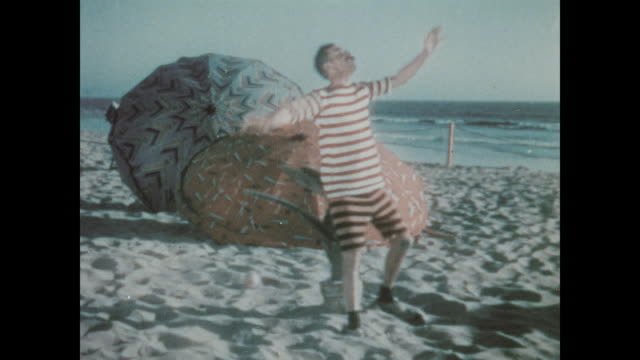 stockvideo's en b-roll-footage met 1930 a man on the beach is unable to catch a ball - achteloos