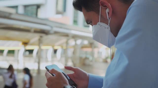 コロナウイルスcovid19マスクを着用して外出先の男。 - 受話器点の映像素材/bロール