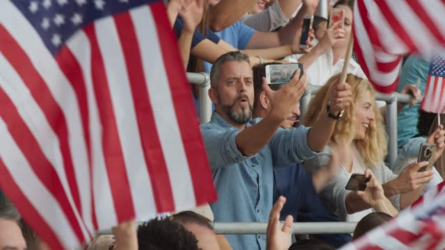 vidéos et rushes de man on the stadium tribune making a smartphone video while spectators wave with american flags - filmer