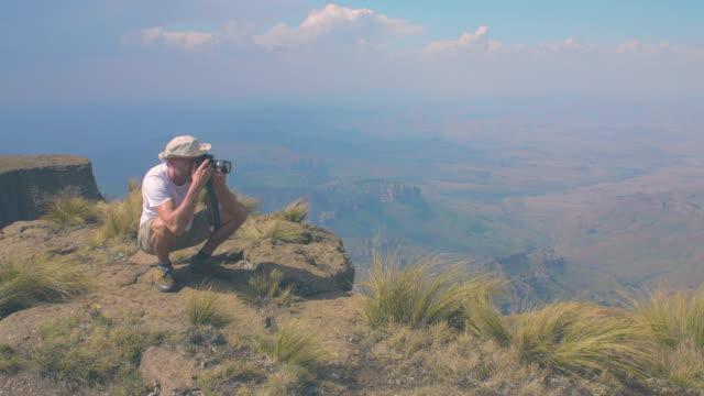 man on top of a mountain takes pictures - drakensberg mountain range stock videos & royalty-free footage