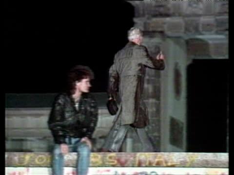 stockvideo's en b-roll-footage met man on top of berlin wall at brandenburg gate being soaked by fire hoses in attempt to get him to climb down opening of berlin wall; 09 nov 89 - berlijnse muur