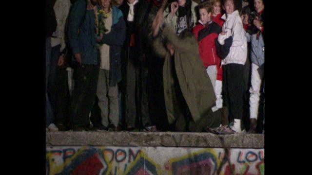vídeos de stock e filmes b-roll de man on top of berlin wall hammering away at it when the berlin wall fell 1989 - muro circundante