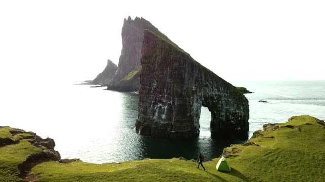 man on top of the cliff at faroe islands - optical illusion stock videos & royalty-free footage