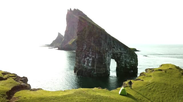 man on top of the cliff at faroe islands - stationary stock videos & royalty-free footage