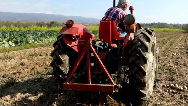 man on tractor in field - pensionati lavoratori video stock e b–roll