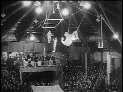 B/W 1955 man on trapeze flipping + being caught by second man swinging on trapeze in circus