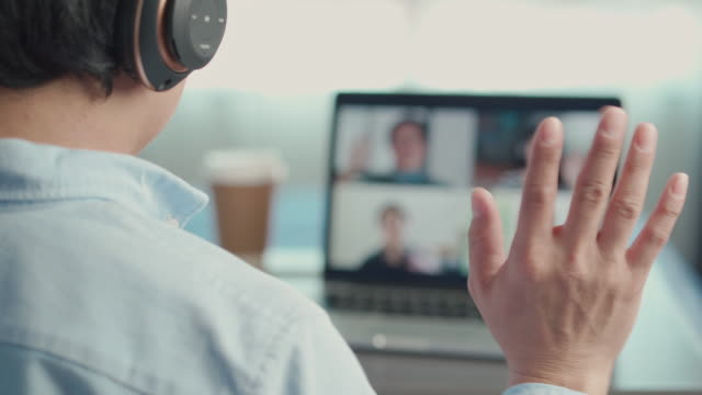 man on video conferencing and waving hands with team, working from home - greeting stock videos & royalty-free footage