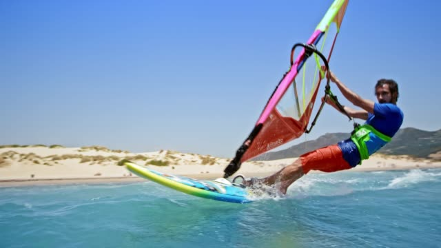 SLO MO Man on windsurf passing by in sunshine