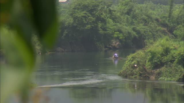 WS SELECTIVE FOCUS Man on wooden raft fishing in river, Guilin, Guangxi Zhuang Autonomous Region, China
