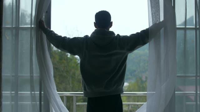 vídeos y material grabado en eventos de stock de hombre cortina abierta buscando paisaje de montaña - ventana