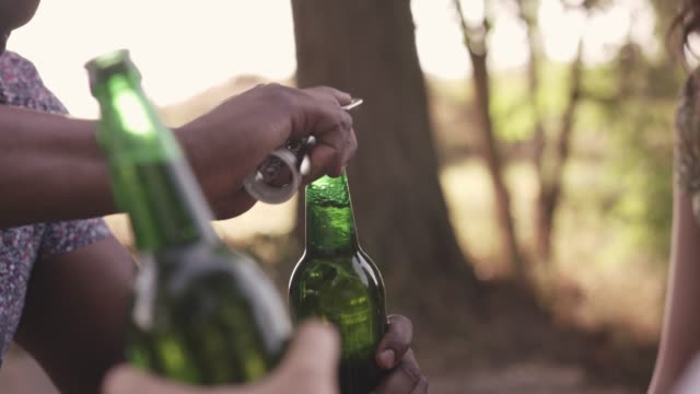 man opening a bottle of beer while relaxing in the nature - bottle opener stock videos & royalty-free footage
