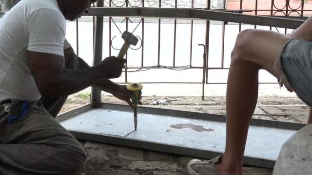 Man opening a hole in a metallic table for installing a sink The table is to be used for a small private cafeteria After economic changes in the...