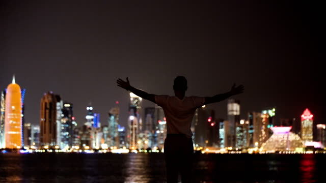 man opening arms facing city by night - arms outstretched stock videos & royalty-free footage