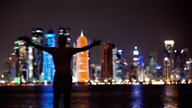 Man Opening Arms Facing City by night
