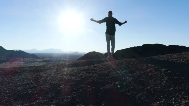man opening arms on a mountain peak. aerial view - rock stock videos & royalty-free footage
