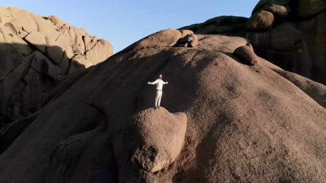 man opening arms on a mountain peak. aerial view - arms outstretched stock videos & royalty-free footage