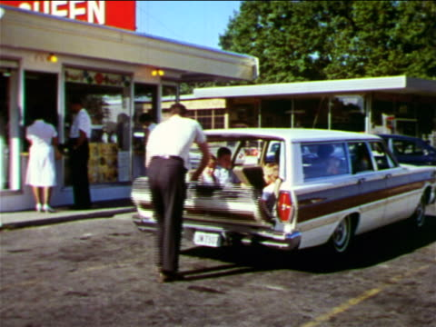 1965 man opening back of ford station wagon to let children out in parking lot / industrial - ford motor company stock videos and b-roll footage