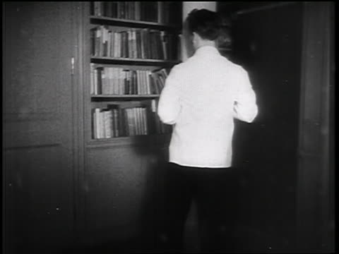 vidéos et rushes de b/w 1935 man opening bookcase + revealing murphy bed behind it / educational - 1935