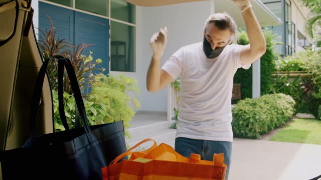 vídeos de stock e filmes b-roll de man opening car trunk and get the grocery bag. - confinamento