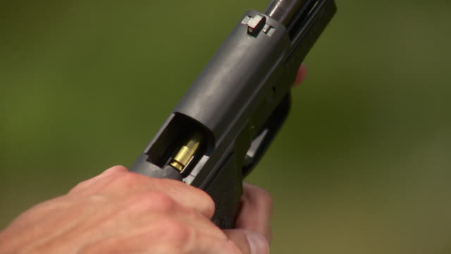 CU HA Man opening chamber of 44 caliber handgun, Stowe, Vermont, USA
