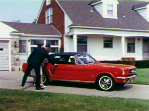vídeos de stock, filmes e b-roll de 1965 man opening door of ford mustang for woman in formalwear in front of suburban house / indust. - 1965
