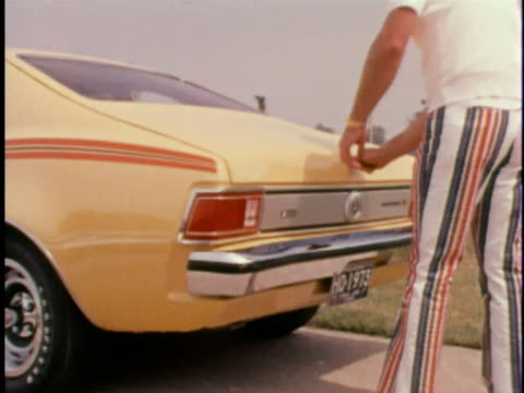 MONTAGE MS man opening hatchback of yellow AMC Hornet/ MS Man removing packages/ USA