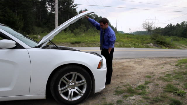 vidéos et rushes de ms man opening hood of broken down car and talking on mobile phone on side of road / portland, me, united states - panne de voiture