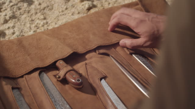 Man opening knife pouch.